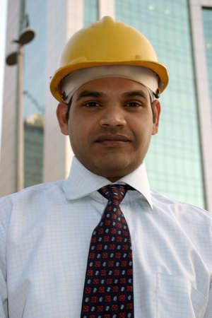 portrait of young indian architect on building construction site  photo