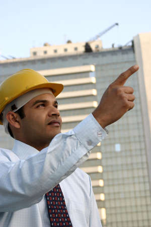 Young Indian Engineer with Vision looking up and pointing at a high rise building photo