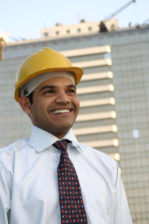 portrait of young indian enginner on building construction site  photo