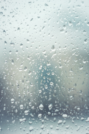 Rain drops on glass with blue tint blur