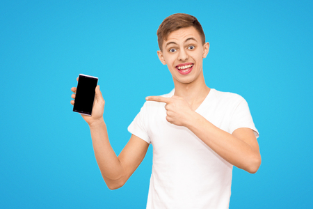 the guy in the white T-shirt advertises the phone isolated on a blue background, the man holds the phone screen in the camera, the place is under the inscription Фото со стока