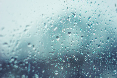 Rain drops on glass with blue tint