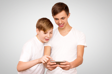 two guys in white t-shirts are playing video games on friends on a gray background, friends have fun