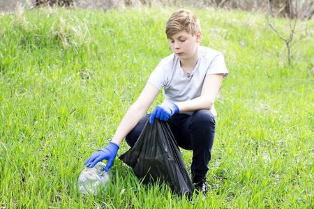 guy volunteer picks up trash on green grass. Spring subotnik cleaning teretorii. Guy takes care of nature