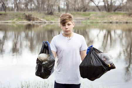 young volunteer guy picks up trash on the banks of the spring river. Global problem. Spring cleaning area