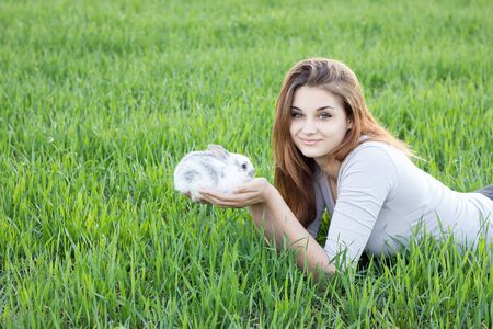 Girl holding a rabbit while on a green meadow. Young smiling girl holding a little fluffy white rabbit. Friendship with Easter Bunny. Spring photo with beautiful young girl with her Bunny Reklamní fotografie