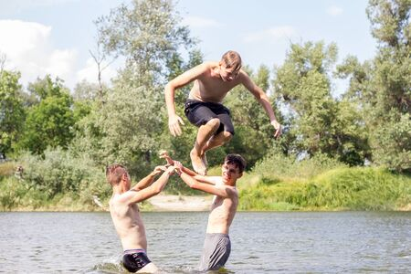 Jumping in the water. Kids have fun and splash in the water. Summer holiday concept , three friends are having fun on the river