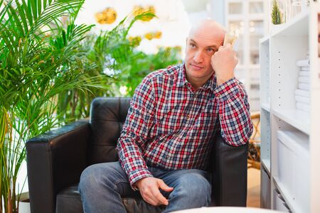 bald european man in a red checked shirt and blue jeans sits in an armchair in a bright apartment with green plants in the background, thoughtful with a book in his hands