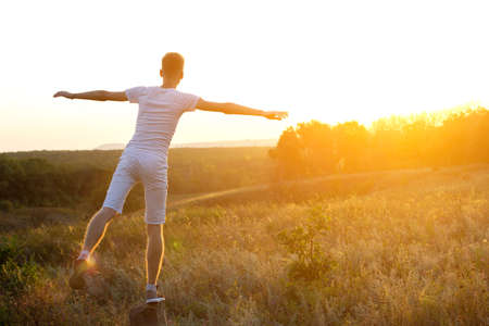 A young boy, dressed in a light T-shirt and shorts, with open arms against the setting sun. Fantastic sunset and beautiful sky in the background. Active life concept.