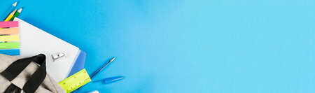 Dropped color school supplies from a gray backpack on a blue background. Photo banner. Place for text.