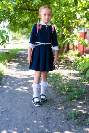 Little schoolgirl girl, dressed in a blue uniform, with two pigtails and a pink backpack on her shoulders, in white socks on an autumn background. School concept.