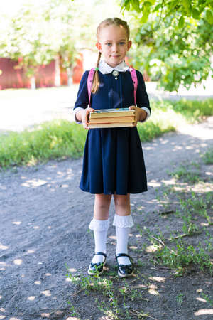 A little schoolgirl girl with two pigtails, dressed in a blue uniform, with a pink backpack on her shoulders and white socks, holds books in her hands against the background of nature.