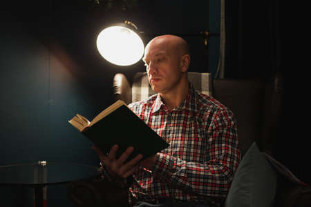 An adult man learns by reading a book in focus at night by the light of a lamp. A dark room.