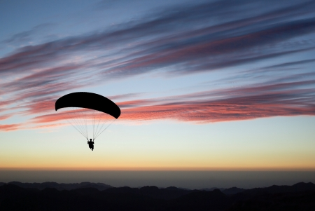 Paraglider pilot fly on sunset  Stock Photo