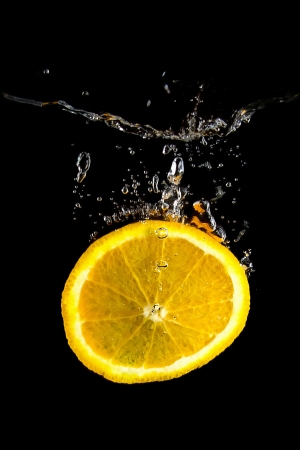 Slice of orange in the water on black background Stock Photo - 17180157