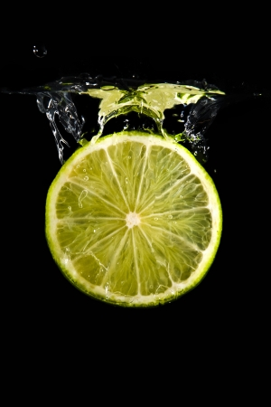 lime drop into water on black Stock Photo - 17180150