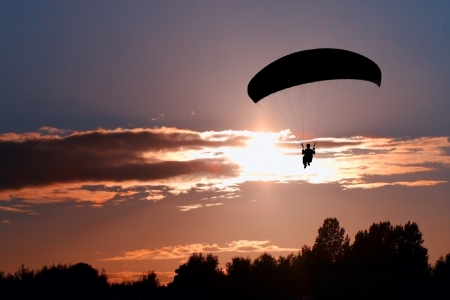 Silhouet paraglider piloot op zonsondergang Stockfoto