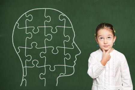 niños pensando: Puzzle de cabeza en la pizarra verde