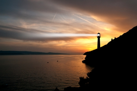 lighthouse keeper: Lighthouse searchlight beam through marine air at night