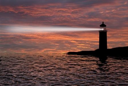Vuurtoren zoeklicht bundel door marine lucht 's nachts Stockfoto