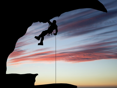 Mountain climber hanging on a rope on the  Stock Photo
