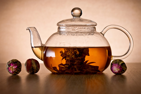 Teapot and glass cup with blooming tea flower photo