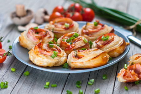 Puff pastry rolls with ham and chese. Baked snacks.