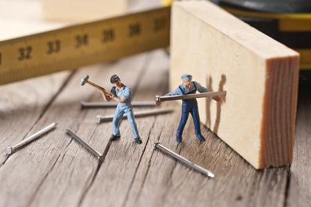 2 つの労働者の棒を爪します。チームワークの概念。