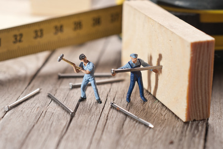 Two workers sticks nail. The concept of teamwork. Stock Photo