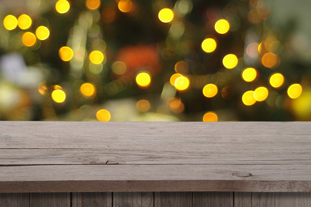 holiday lights display: Christmas holiday or party background with empty wooden deck table over festive bokeh. Ready for product montage