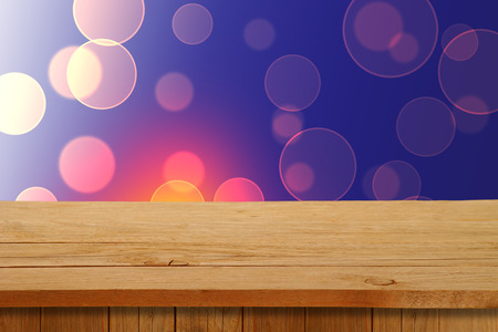 christmas display: Christmas holiday or party background with empty wooden deck table over festive bokeh. Ready for product montage