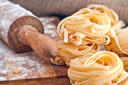yellow flour: Homemade tagliatelle. Raw pasta on the wooden table.