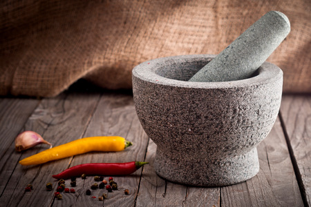Stone Mortar on a wooden bench photo