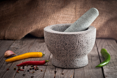 pepper grinder: Stone Mortar on a wooden bench