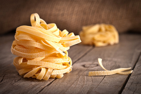 ribbon pasta: Homemade tagliatelle. Uncooked pasta on the wooden table. Stock Photo