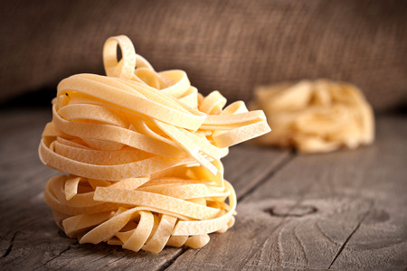 Homemade tagliatelle. Uncooked pasta on the wooden table. Stock Photo
