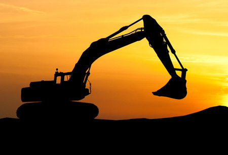 silhouette of Excavator loader at construction site with raised bucket over sunset 스톡 콘텐츠