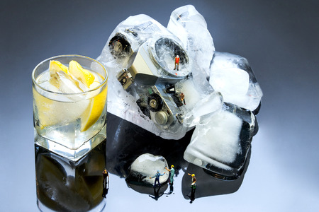 Tiny figurines crack ice to drink. The concept of cooking Stock Photo