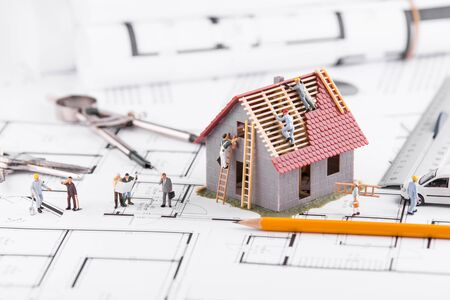 Winzige Leute bauen Häuser für architektonische Pläne. Das Konzept der Teamarbeit.