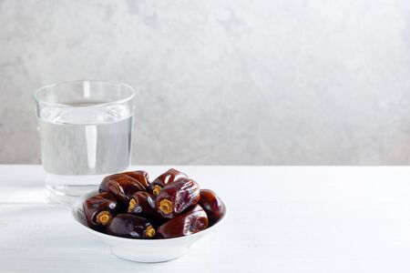 Dates and a glass of water on white wooden table. Ramadan, Iftar concept. Horizontal, copy space.