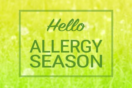 Natural green grass and flowers background and Hello allergy season text. Spring summer seasonal pollen allergy concept.