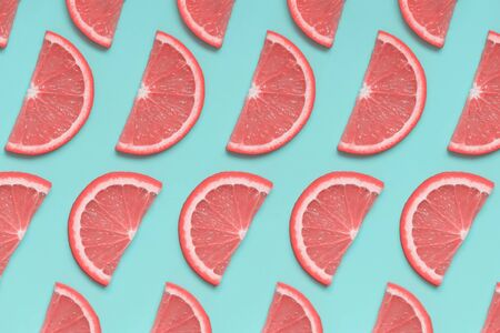 Pink grapefruit isometric pattern on pastel blue background. Minimal summer fruit concept, pop art style. Flat lay, top view. 스톡 콘텐츠