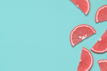 Citrus fruit slices with color flesh texture on pastel turquoise background. Summer fruit minimalism. Top view, flat lay, copy space for text. 스톡 콘텐츠