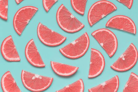 Creative summer pattern with grapefruit slices on pastel blue background. Minimal healthy food, color trend concept. Pop art style. Top view, flat lay. 스톡 콘텐츠