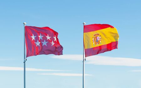 Madrid region and Spain flags on flag poles waving on blue sky background