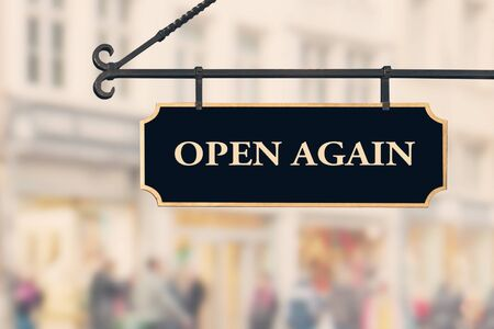 Open again sign board against open shop windows background. Restarting business after coronavirus quarantine lockdown. Economy reopening concept