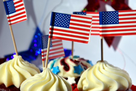 Happy Independence Day celebration and patriotism holidays concept - close up of glazed muffins or cupcakes decorated with American flags at 4th of july party