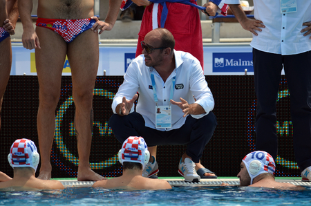 waterpolo: Budapest, Hungary - Jul 14, 2014. Ivica Tucak (head coach) talking to the croatian team. The Waterpolo European Championship was held in Alfred Hajos Swimming Centre in 2014.