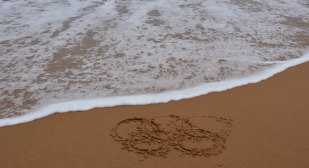 approaches: Sydney, Australia - Jul 31, 2016 Wave Approaches Olympic rings drawn in the sand. Rio Summer Olympic Games 2016th