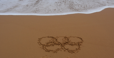 the olympic rings: Sydney, Australia - Jul 31, 2016 Wave Approaches Olympic rings drawn in the sand. Rio Summer Olympic Games 2016th